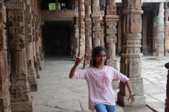 Qutub Minar - Gayathri is on a dance posture between the beautiful pillars